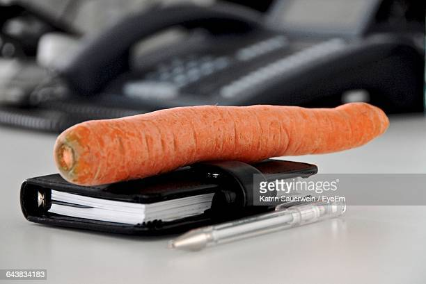 Close-Up Of Carrot And Book On Table