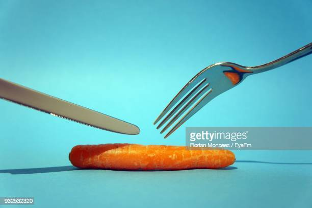 Close-Up Of Carrot And Eating Utensils Over Blue Background