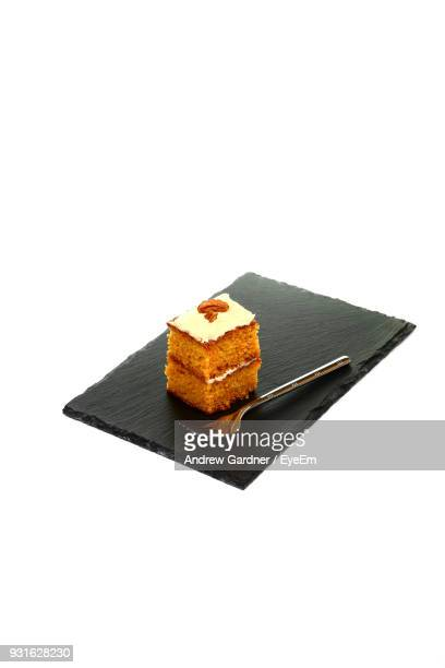 Close-Up Of Carrot Cake On Slate Over White Background