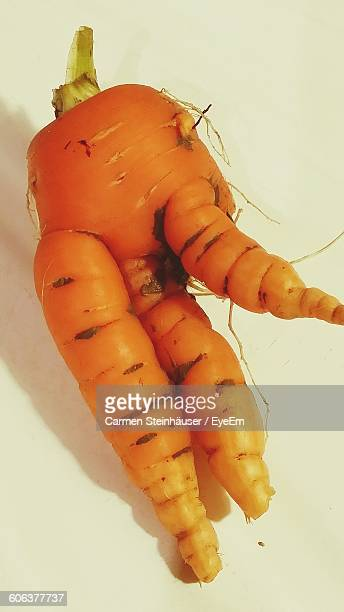 close-up of carrot on white table - imperfection stock pictures, royalty-free photos & images