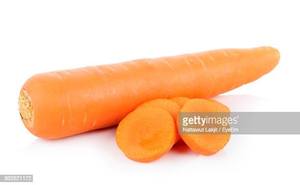 Close-Up Of Carrot With Slices Against White Background