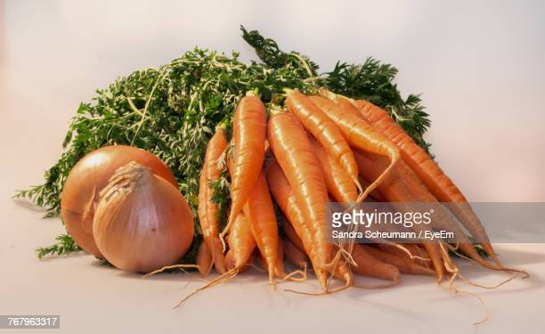 Close-Up Of Carrots And Onions On Table