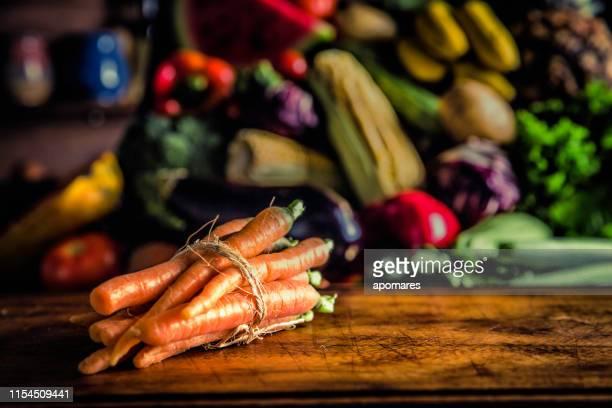 gros plan de carottes aux fruits et légumes tropicaux dans une cuisine rustique. éclairage naturel - fruit exotique photos et images de collection