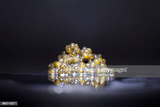 close-up of caviar on table against black background - caviar stock photos and pictures