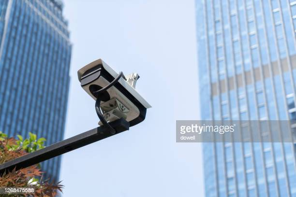 close-up of cctv near modern building - business security camera stock pictures, royalty-free photos & images