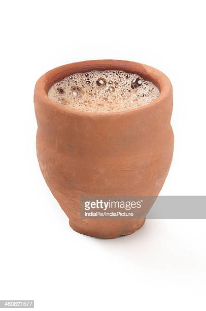 Close-up of chai in traditional cup made of clay isolated over white background