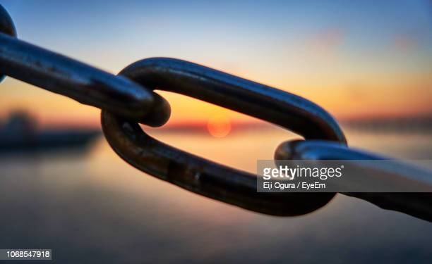 close-up of chain against sea during sunset - durability stock photos and pictures