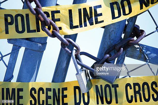 Closeup of chain locked gate covered with yellow police tape