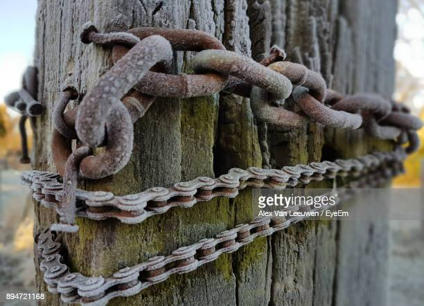Close-Up Of Chain On Weathered Wood