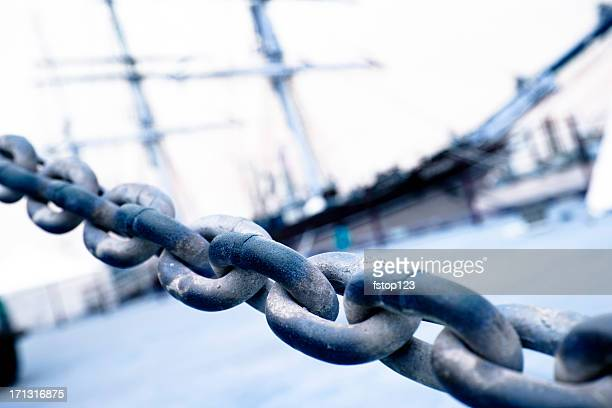 Close-up of chain with tall sailing ship in background. Docks.