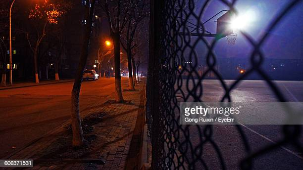 Close-Up Of Chainlink Fence By Illuminated Basketball Court At Night