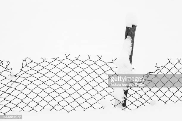 Close-Up Of Chainlink Fence On Snow Covered Field