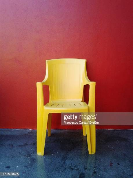 Close-Up Of Chair Against Red Wall At Home