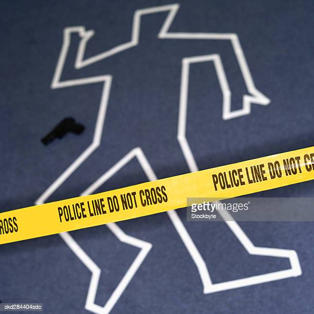 Close-up of chalk outline of body behind police tape