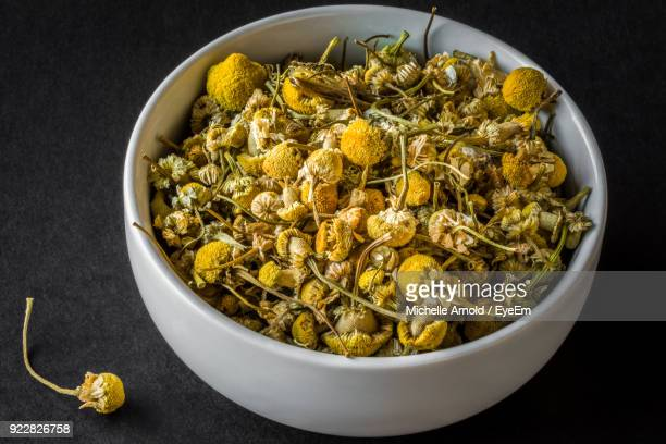 close-up of chamomile in bowl on table - chamomile tea stock photos and pictures