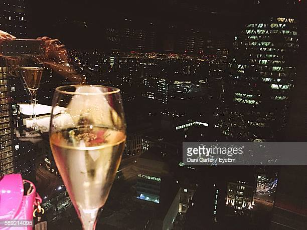 Close-Up Of Champagne Against Buildings At Night