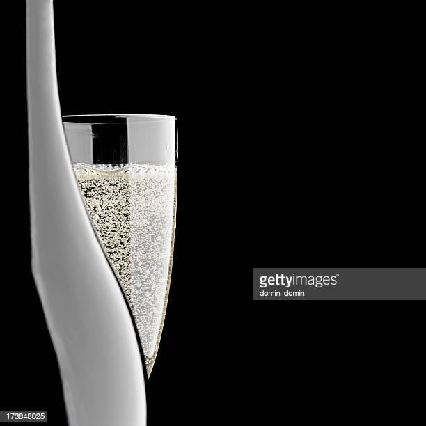 Nahaufnahme von Flasche und Glas Champagner, isoliert auf schwarzem Hintergrund