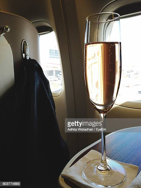 Close-Up Of Champagne Flute In Airplane Against Window