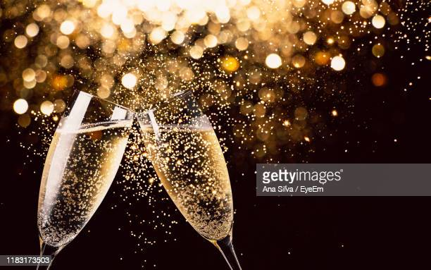 close-up of champagne flutes against black background - champagne stock pictures, royalty-free photos & images