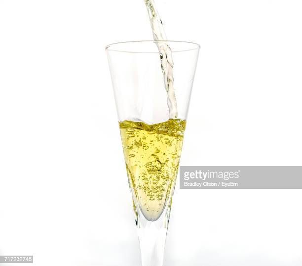 Close-Up Of Champagne Pouring In Flute Against White Background