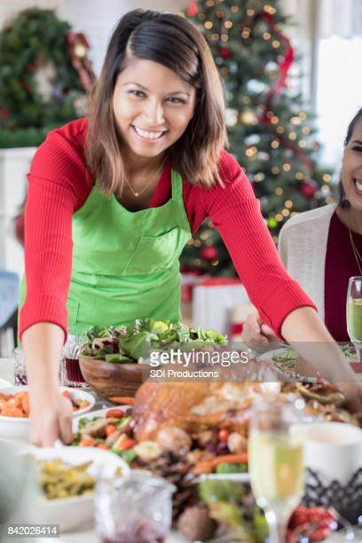 Closeup of Cheerful Christmas dinner hostess bringing Turkey