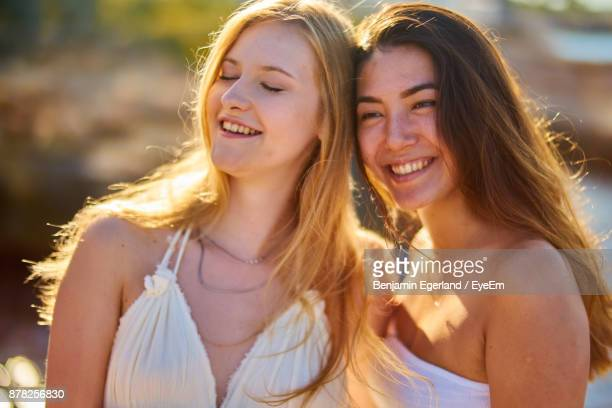 Close-Up Of Cheerful Female Friends Standing Outdoors During Sunset