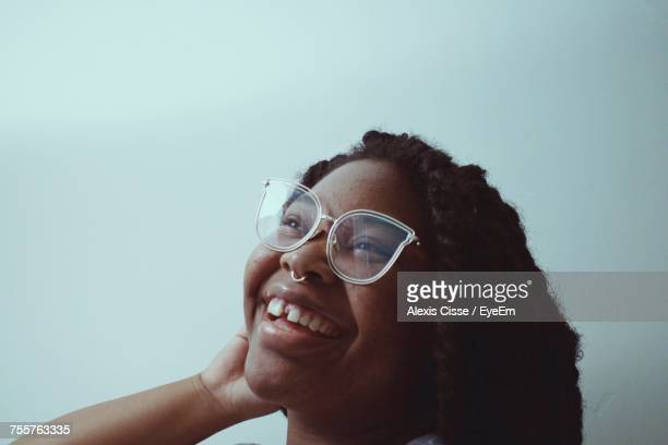 close-up of cheerful girl wearing eyeglasses by white wall - nose piercing stock pictures, royalty-free photos & images