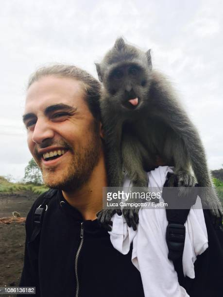 close-up of cheerful man with monkey on shoulder - monkey man stock pictures, royalty-free photos & images