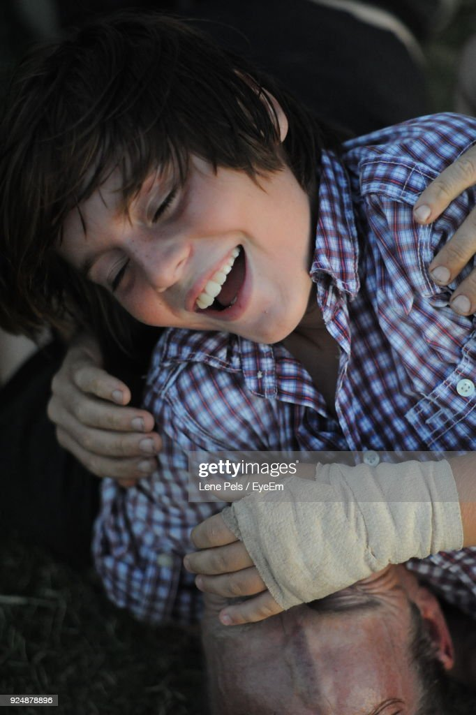 Close-Up Of Cheerful Teenager With Injured Hand Falling On Father At Field : Stock Photo
