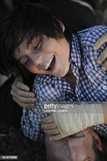 close-up of cheerful teenager with injured hand falling on father at field - lene pels stockfoto's en -beelden