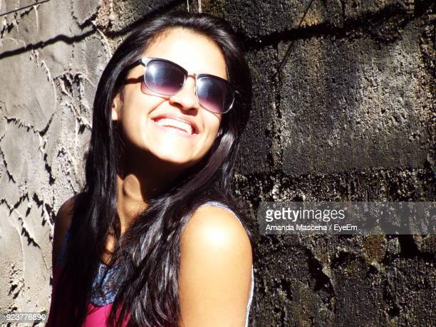 Close-Up Of Cheerful Woman Wearing Sunglasses By Wall