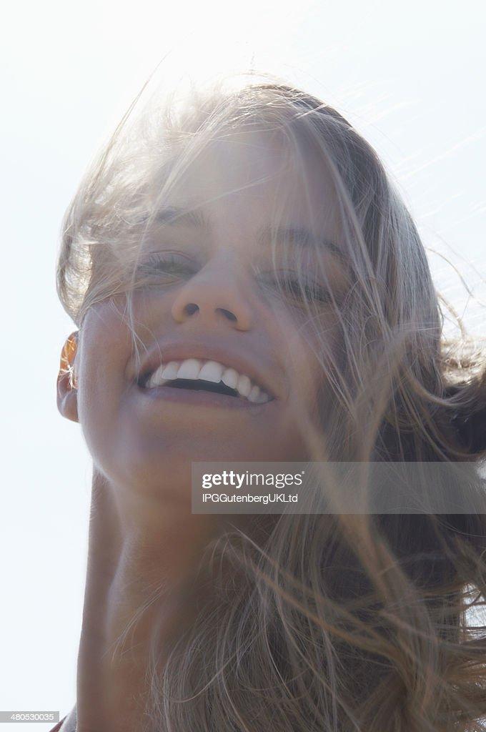 Gros plan d'une joyeuse femme avec des cheveux vent : Photo