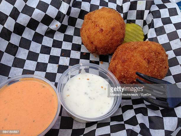 Close-Up Of Cheese Balls With Sauce Served On Checked Paper
