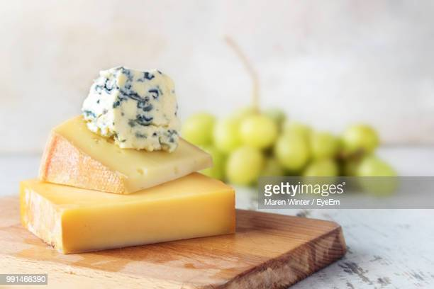 close-up of cheese on cutting board at table - cheese stock pictures, royalty-free photos & images