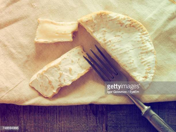 Close-Up Of Cheese With Fork On Wooden Table