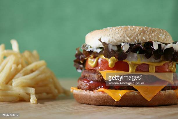 Close-Up Of Cheeseburger With French Fries On Table