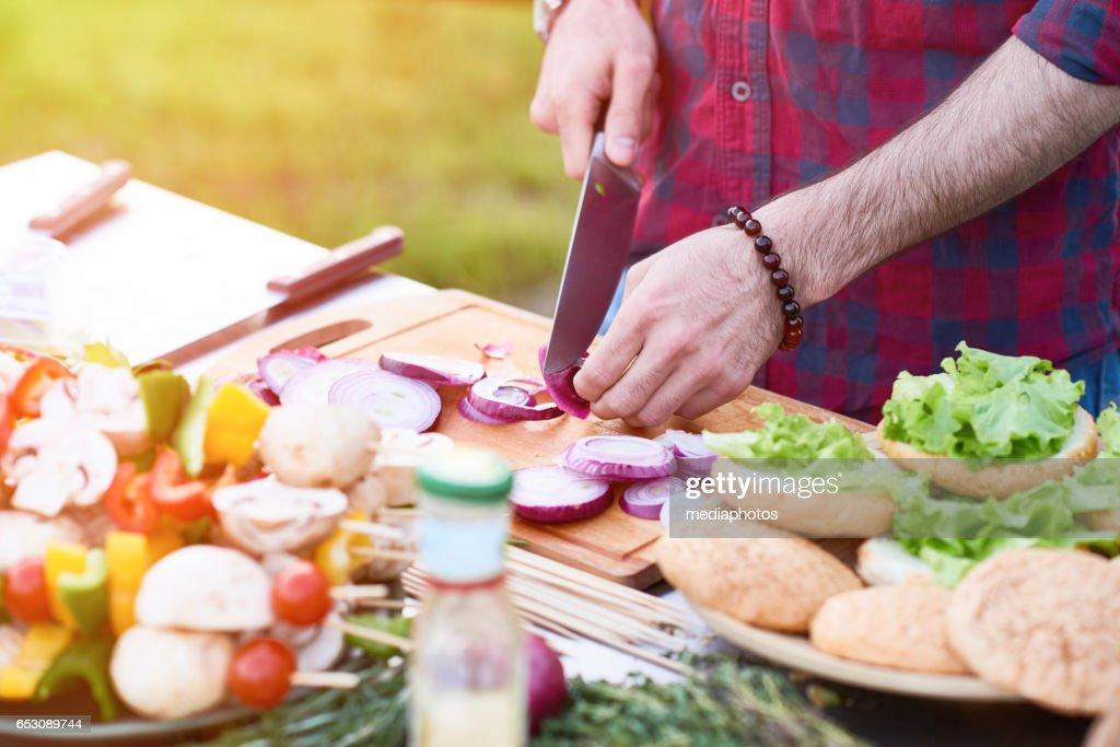 Close-up van chef-kok snijden van rode ui aan boord van buitenshuis : Stockfoto