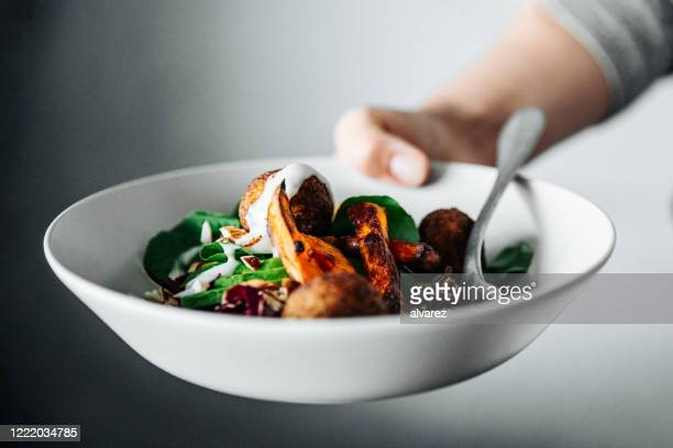 close-up of chef holding a vegan falafel bowl - giving stock pictures, royalty-free photos & images