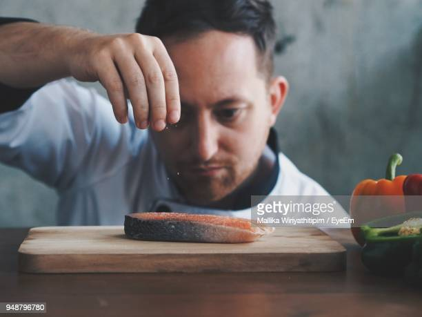 Close-Up Of Chef Pouring Salt On Meat