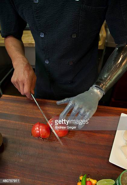 Closeup of chef with prosthetic hand cut tomatoes.