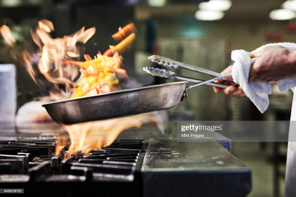 Close-up of chefs hands holding a saute pan to cook food, flambeing contents. Flames rising from the pan. : Stock Photo