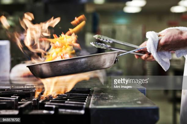 Close-up of chefs hands holding a saute pan to cook food, flambeing contents. Flames rising from the pan.