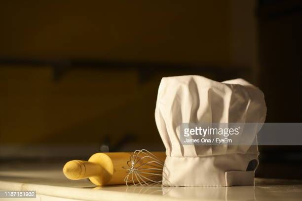 close-up of chefs hat with wire whisk and rolling pin on table - chef's hat stock pictures, royalty-free photos & images