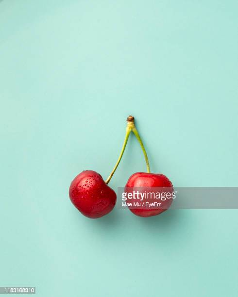 close-up of cherries against turquoise background - cherry stock pictures, royalty-free photos & images