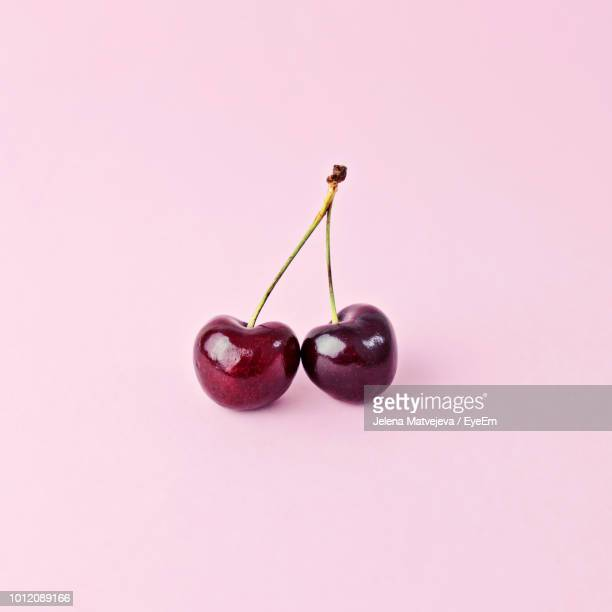 Close-Up Of Cherries Over Pink Background