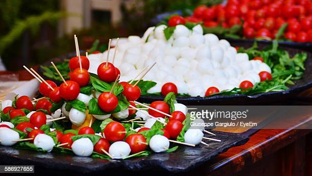 Close-Up Of Cherry Tomato And Mozzarella With Basil Leaf In Toothpicks