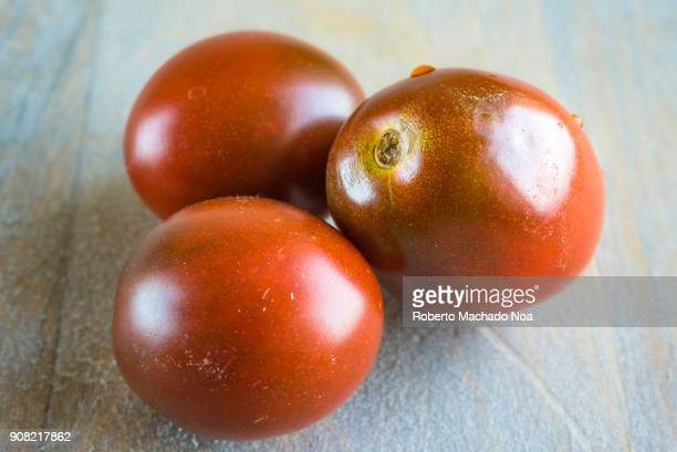 Closeup of Cherry Tomatoes over a wood background Health benefits of the fruit include being rich in Vitamin C