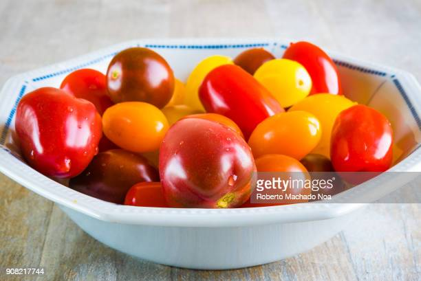 Closeup of Cherry Tomatoes The mixture of varieties is on a small recipient and over a wood background Health benefits of the fruit include being...