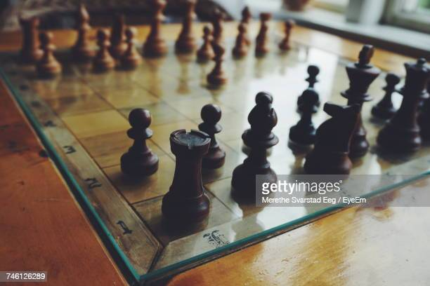 Close-Up Of Chess Board With Pieces On Wooden Table