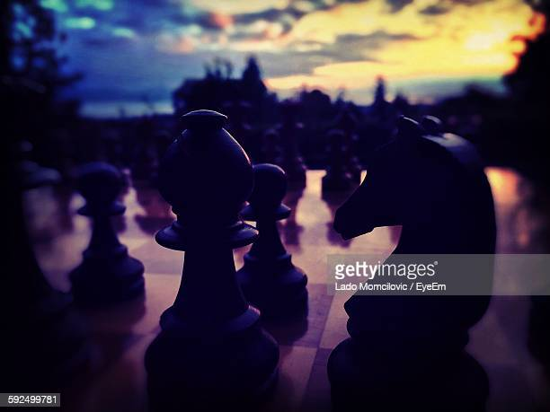 Close-Up Of Chess Pieces Against Sky During Sunset